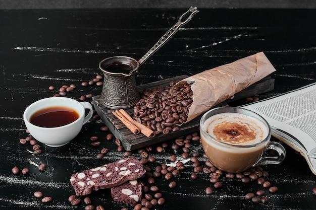 Кофейные зерна на черном фоне с чашкой напитка.