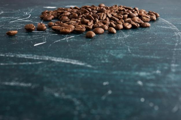 Кофейные зерна на синем столе.