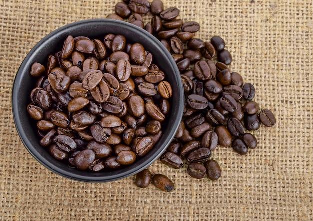 Кофе в зернах на чашу положить на мешок, вид сверху