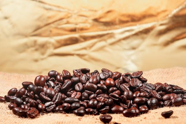 茶色のリネン生地の背景にコーヒー豆。背景として使用されるローストコーヒー豆のテクスチャ。フラット横たわっていた、トップビュー、コピースペース。