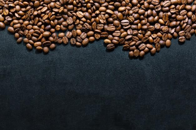 暗い背景にコーヒー豆。上面図。コーヒーのコンセプト。