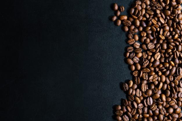 Кофейные зерна на темном фоне. вид сверху. концепция кофе.