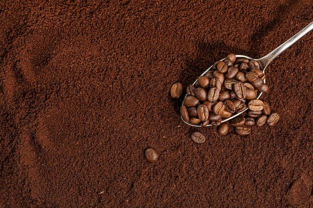 挽いたコーヒーの背景にスプーンでコーヒー豆。閉じる。