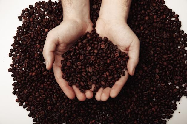 他のコーヒー豆を背景にハートの形をした手のひらにコーヒー豆。