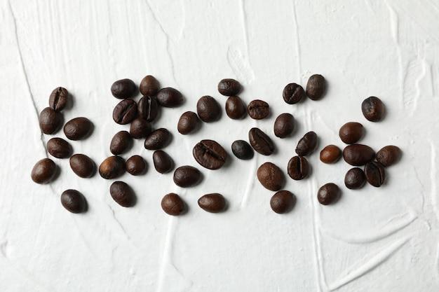 Кофейные зерна на белом фоне, вид сверху и место для текста