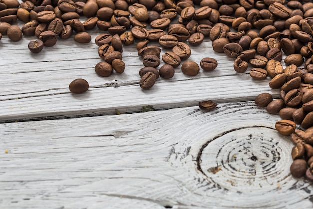 Кофейные зерна на белой деревянной стене, крупным планом