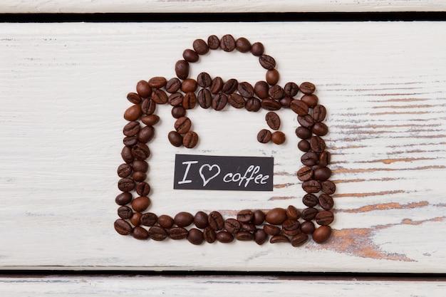 핸드백 모양으로 배열하는 나무에 커피 콩. 커피 사랑 개념. 표면에 흰색 나무입니다.