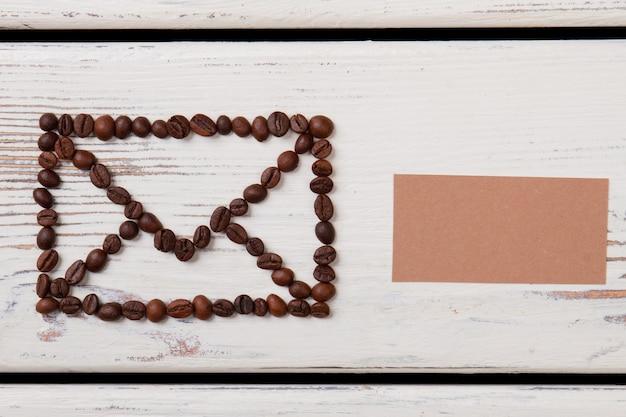 봉투 기호에 배열하는 나무에 커피 콩. 상위 뷰 흰색 배경입니다.