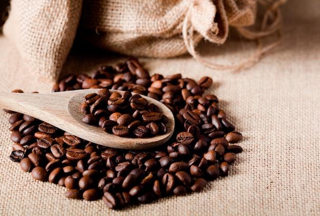 Кофейные зерна на деревянной ложке, с мешком из ткани рафии