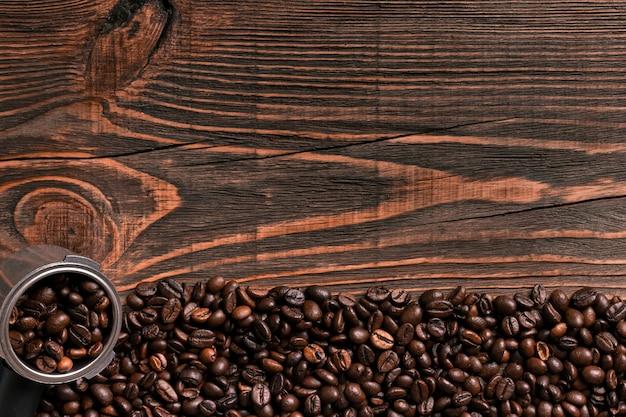 コピースペースと木製のテーブルテクスチャのコーヒー豆。上からの眺め。静物。フラットレイ。モックアップ