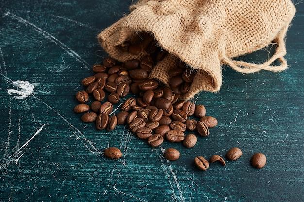 Chicchi di caffè da una tasca rustica.