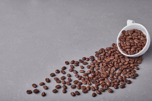 Chicchi di caffè da una tazza bianca.