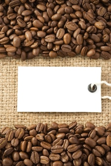 Coffee beans and paper price tag on sack burlap texture
