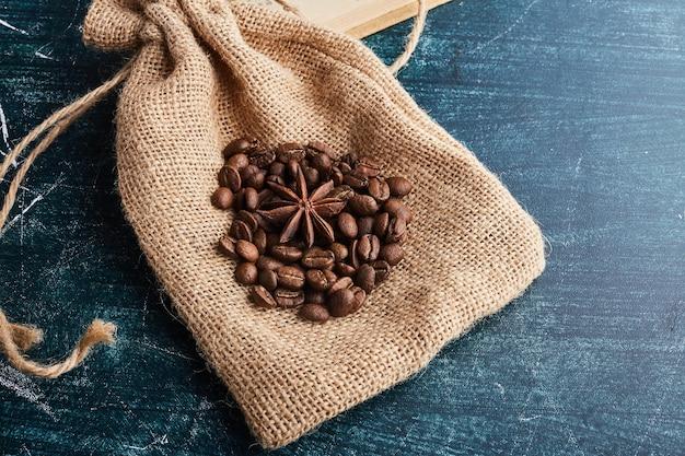Chicchi di caffè su un pezzo di tela da imballaggio.