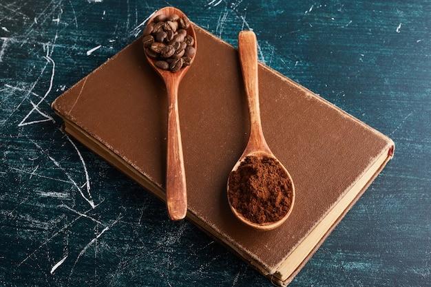 Chicchi di caffè e polvere in cucchiai di legno.