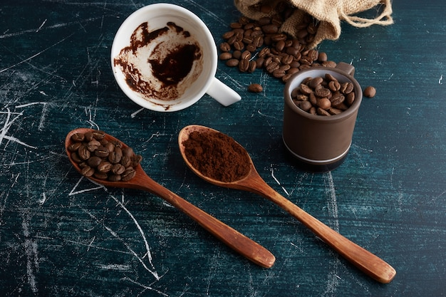 Coffee beans and powder in wooden spoons.