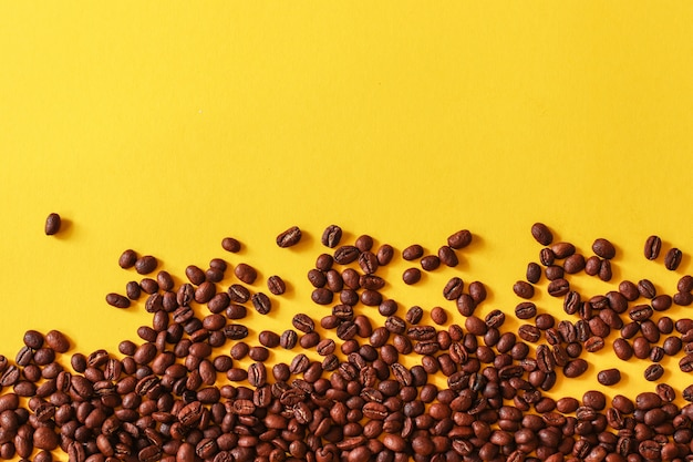 Coffee beans randomly scattered on yellow background.