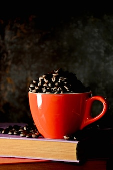 Coffee beans in red cup on old book in the kitchen room at the morning