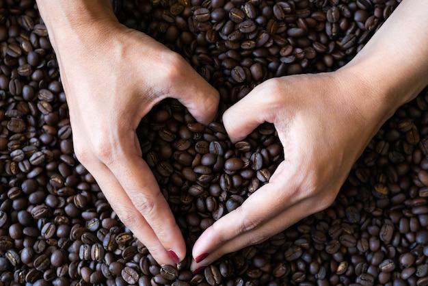 ハート型の手を握っている女性にコーヒー豆を焙煎コーヒー豆背景テクスチャ