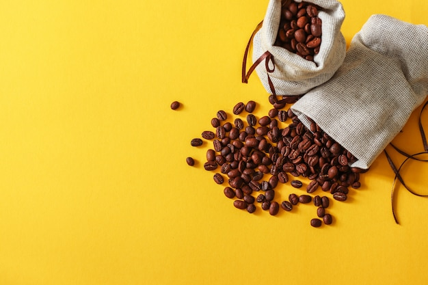 Coffee beans in sacks on yellow background with copy space for your text.