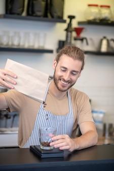 コーヒー豆。素晴らしい気分でバーで紙袋からきれいなガラスにコーヒー豆を注ぐエプロンで満足した男