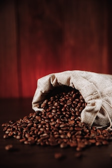 Coffee beans scattered of the bag on wooden table. vertical image.