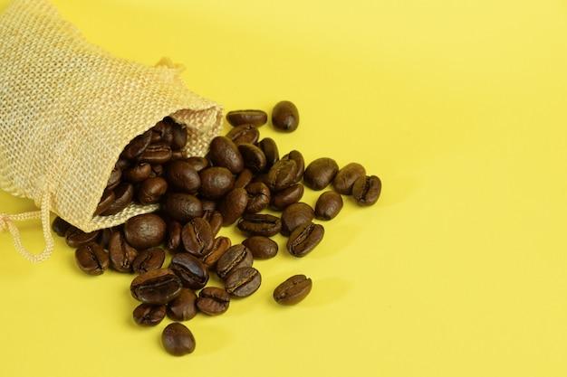 Кофейные зерна разбросаны из небольшого мешочка на желтом фоне с левой стороны.