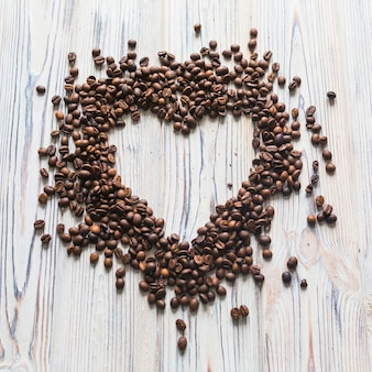 Coffee beans scattered in shape of heart