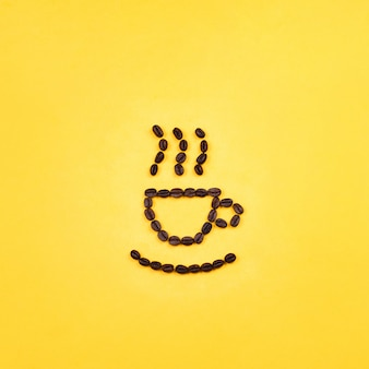 Coffee beans in a shape of a cup and steam. concept of good morning, yellow background, flat lay