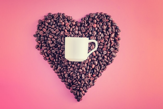 Coffee beans in shape of heart and white cup on pink background