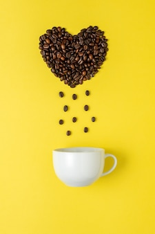 Coffee beans in shape of heart with white cup on yellow surface.