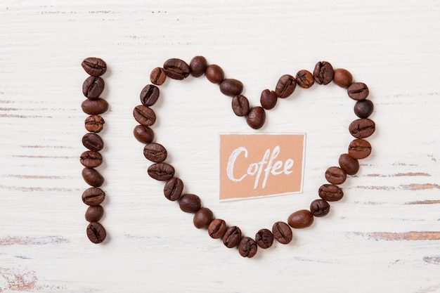 Coffee beans in a shape of i letter and heart. coffee word in a heart made coffee beans. white wooden surface.