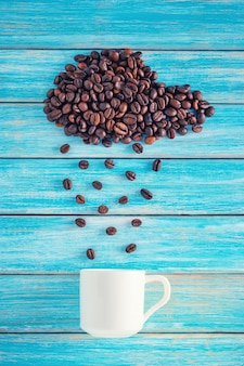 Coffee beans in shape of rainy cloud with cup on blue background. weather concept