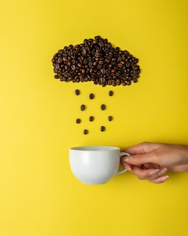 Coffee beans in shape of rainy cloud with white cup on yellow surface.