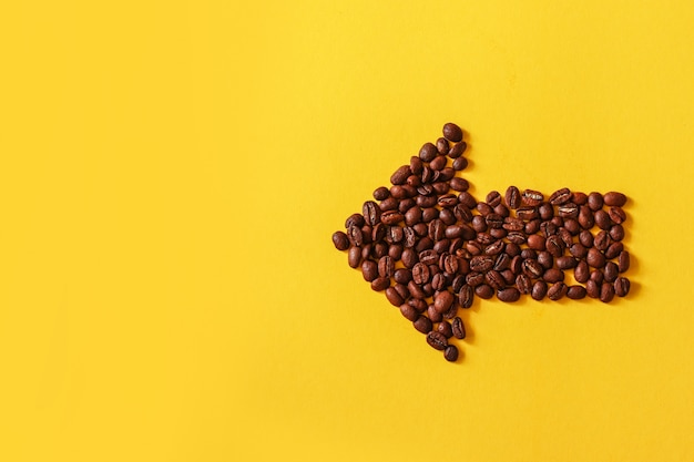 Coffee beans shaped in form of arrow isolated on yellow background.