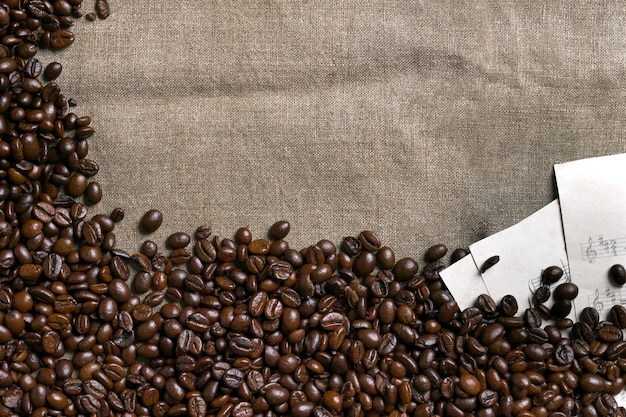 Coffee beans and sheet music on burlap background
