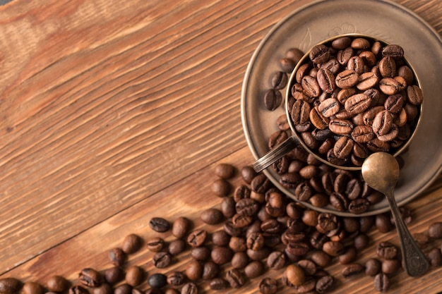 Coffee beans in a silver cup on wooden  table