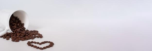白い背景の上のカップからコーヒー豆がこぼれます。横バナー