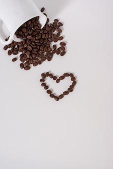白い背景の上のカップからコーヒー豆がこぼれる