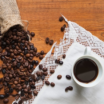 Кофейные бобы, пролитые возле чашки