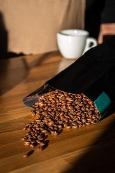 木製の背景に袋からこぼれたコーヒー豆