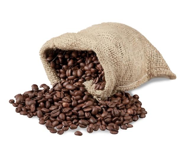 白い背景の上の袋からこぼれるコーヒー豆