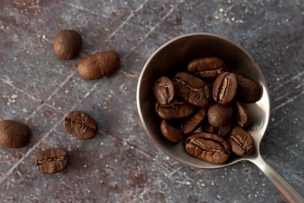 Chicchi di caffè sul cucchiaio con fondo di marmo