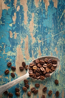 Coffee beans in a spoon on wooden
