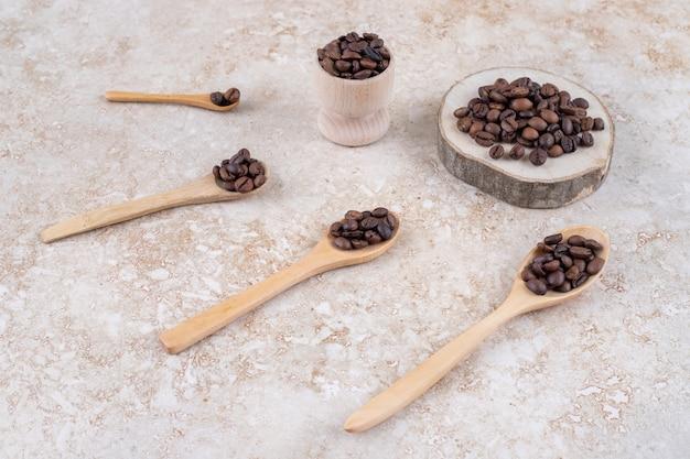 Chicchi di caffè su cucchiai, un pezzo di legno e una tazzina