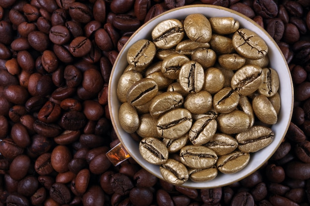 Coffee beans texture background. golden coffee beans in a cup. golden coffee as a symbol of quality and luxury. the concept of luxury and originality. top view