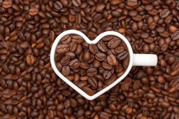 Кофейные зерна белая сердечная кружка с кофейными зернами на фоне кофейных зерен