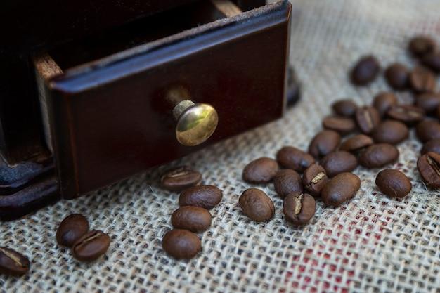 Кофейные зерна с деревянной кофемолкой на мешковине. приготовление ароматного напитка. крупный план.