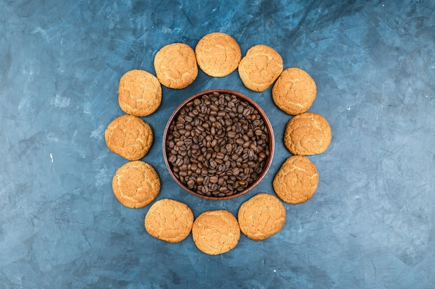 Coffee beans with biscuits on dark blue background