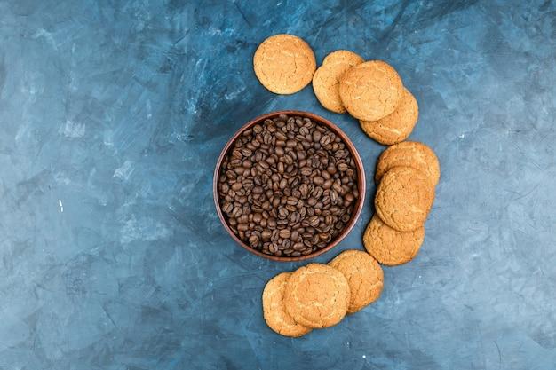 진한 파란색 배경에 비스킷과 커피 콩